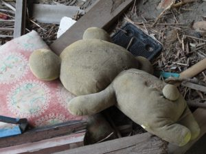 A teddy bear atop a pile of tsunami debris.