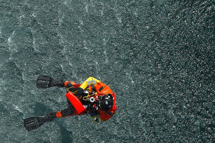 U.S. Coast Guard Petty Officer 2nd Class Charles Mitchell, a rescue swimmer from Coast Guard Air Station Cape Cod, Mass., is hoisted back into an HH-60 Jayhawk helicopter after retrieving Oscar, a rescue training dummy, 50 miles east of Boston, Mass., on March 25, 2008.
