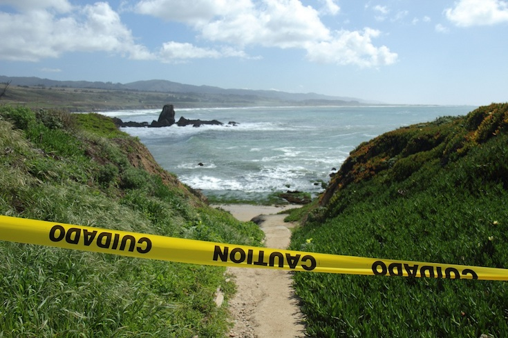 Beach with caution tape across entrance