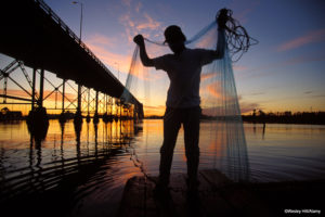 Fisherman getting his net together on the dock under the bridge in Lake Charles Louisiana